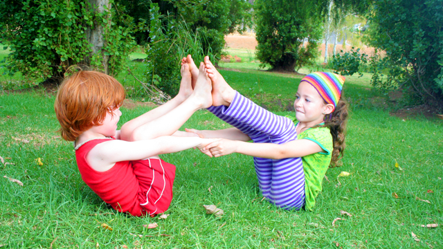 Two children in Double Boat Pose (Navasana)